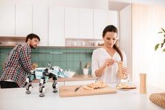 Un type et une fille posent dans une cuisine moderne Est tout près un rhinocéros de robot Ils ont coûté dans la cuisine légère mo Photo libre de droits