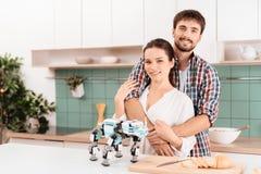 Un type et une fille posent dans une cuisine moderne Est tout près un rhinocéros de robot Ils ont coûté dans la cuisine légère mo Image stock