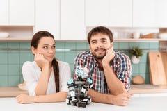 Un type et une fille posent dans la cuisine Ils se penchent sur la table Un robot se repose à côté de eux Ils sourient Photo libre de droits