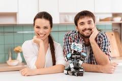 Un type et une fille posent dans la cuisine Ils se penchent sur la table Un robot se repose à côté de eux Ils sourient Photos libres de droits