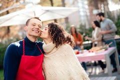 Un type et une fille posent sur l'appareil-photo pendant un pique-nique avec des amis Photo libre de droits
