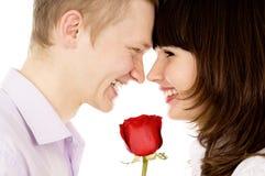 Un type et une fille tenant une rose et un regard à l'un l'autre Photos libres de droits