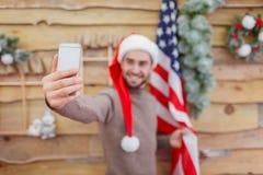 Un type faisant le selfie avec un drapeau américain hors focale près du mur Image stock