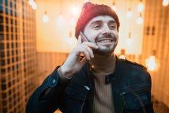 Un type heureux de hippie parlant sur un smartphone Dans la perspective des lampes Photo stock