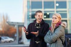 Un type hurle agressivement à une fille par derrière un téléphone portable cassé Photographie stock libre de droits