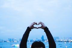 Un type montrant le connexion de main de coeur même avec Bokeh s'allume à l'arrière-plan de ville Photo stock