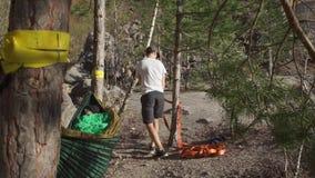 Un type prépare une ligne de slackline pour attacher un arbre banque de vidéos