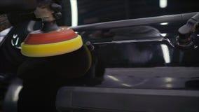 Un type professionnel de travailleur applique le liquide spécial de céramique à la voiture utilisant une éponge d'applicateur dan photos libres de droits