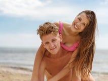 Un type ramenant une fille sur le sien, à la plage, dehors Image en gros plan d'homme et de femme heureux gais Images libres de droits