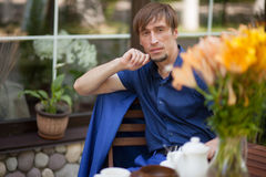 Un type s'asseyant dans un café examinant la distance Image libre de droits