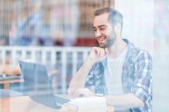 Un type s'asseyant en café utilisant l'ordinateur portable Photographie stock libre de droits
