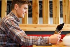 Un type s'assied dans un café avec un comprimé dans des ses mains inside Image stock