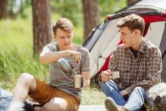 Un type se faisant le thé tout en parlant à son ami Photo libre de droits