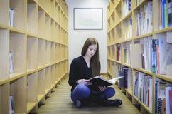 Un'ubicazione della ragazza sul pavimento delle biblioteche Immagine Stock