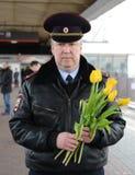 Un ufficiale di polizia con i fiori sul binario della stazione Immagini Stock