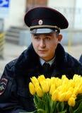 Un ufficiale di polizia con i fiori sul binario della stazione Immagine Stock Libera da Diritti