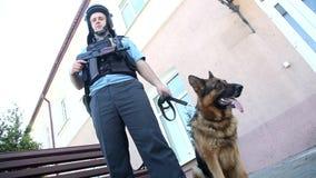 Un ufficiale di polizia con una pistola e un cane video d archivio