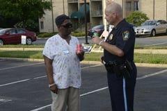 Un ufficiale di polizia parla con afroamericano agli eventi di una comunità immagini stock libere da diritti