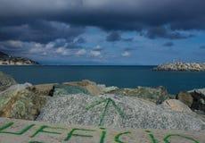 Un ufficio italiano scritto originale sulle rocce al mare Immagine Stock