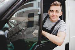 Un uniforme que lleva sonriente hermoso joven del individuo está mirando fuera de la ventanilla del coche Movimiento de la casa,  foto de archivo libre de regalías