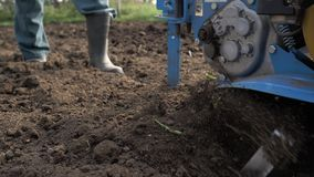 Un uomo è un agricoltore in un'area suburbana, un orto, aratri la terra con un coltivatore, un aratro manuale del motore, argilla video d archivio
