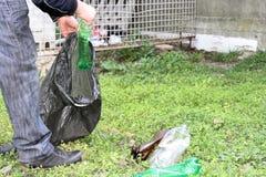 Un uomo è impegnato in ecologia della natura e raccoglie la plastica imbottiglia un sacchetto di plastica che pulisce la terra fotografia stock