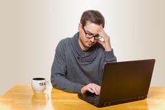 Un uomo è malato dei problemi con il suo computer portatile in cui sta lavorando sopra Fotografie Stock Libere da Diritti