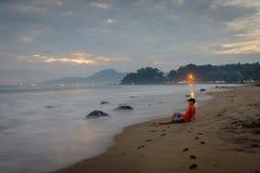 Un uomo è sedentesi e godente del momento sulla spiaggia di Karang Hawu, Java ad ovest, Indonesia immagini stock libere da diritti