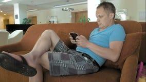 Un uomo è sulla sua metà di compressa del cuscinetto su uno strato stock footage