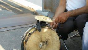 Un uomo abbronzato che gioca sul vecchio tamburo all'aperto archivi video