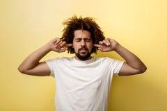 Un uomo abbronzato riccio sta tenendo le sue dita in sue orecchie, occhi è chiuso nella riluttanza per ascoltare Maglietta bianca fotografia stock