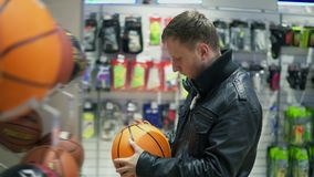 Un uomo adulto in bomber nero che sceglie una palla di pallacanestro per gli sport all'aperto archivi video