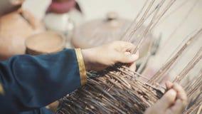 Un uomo adulto in un costume nazionale sta tessendo un canestro Un musulmano anziano sta tessendo un canestro dei ramoscelli Fest archivi video