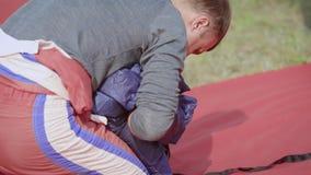 Un uomo adulto piega il suo paracadute video d archivio