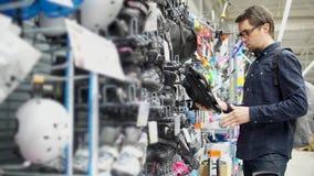 Un uomo adulto sceglie i pattini di rullo per sua figlia, lui è nel centro commerciale archivi video