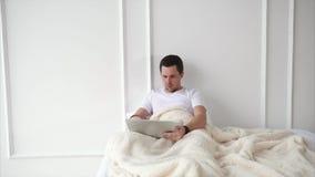 Un uomo adulto tiene un computer portatile e guarda i rapporti di notizie su un aggeggio portatile stock footage