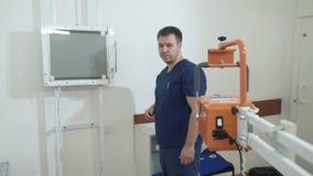 Un uomo adulto in vestiti medici regola l'apparecchiatura di raggi x Medico nell'ospedale lavora con attrezzatura medica stock footage
