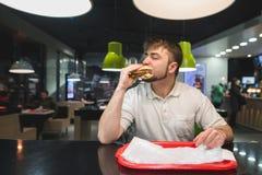 Un uomo affamato mangia un grande hamburger appetitoso ad una tavola in un fast food Concetto degli alimenti a rapida preparazion Immagine Stock Libera da Diritti