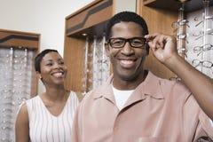 Un uomo afroamericano che prova sui vetri Immagine Stock