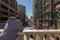Un uomo afroamericano con una maglietta felpata bianca riposa su un corrimano alla via del cespuglio a San Francisco, la Californ fotografie stock