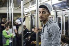 Un uomo afroamericano stanco e giovane guida il sottopassaggio di NYC fotografie stock libere da diritti