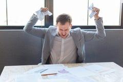 Un uomo aggressivo grida irosamente, schiacciando le carte con i documenti All'interno nell'ufficio immagine stock libera da diritti