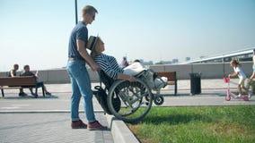 Un uomo aiuta una ragazza in una sedia a rotelle a andare giù dal bordo all'asfalto Un uomo sta spingendo una sedia a rotelle video d archivio