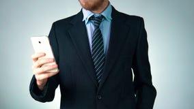Un uomo alla moda in un vestito sta tenendo un telefono Elegante, affare, socievole stock footage
