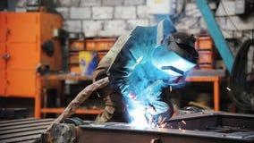Un uomo alle parti di metallo delle saldature della pianta video d archivio