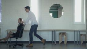 Un uomo allegramente trasporta una donna l'ufficio su una sedia video d archivio