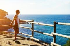 Un uomo alto con sport calcola, facendo allungando stare su una roccia ed ammira la vista del mare Fotografia Stock