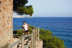 Un uomo alto con sport calcola, facendo allungando stare su una roccia ed ammira la vista del mare L'atleta moro caldo fotografia stock libera da diritti