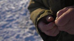 Un uomo anziano attacca il motht al gancio di pesca Pesca di inverno 4K archivi video