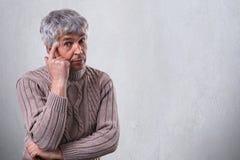 Un uomo anziano bello con le grinze si è vestito in maglione che ha espressione triste e premurosa che giudica il suo dito sul su Fotografie Stock